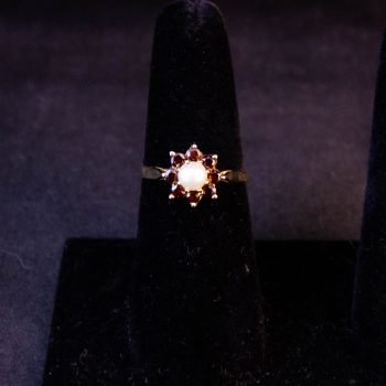 9k yellow gold ring with pearl centre surrounded by garnets. Size O1/2 Price includes delivery