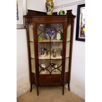 Unusual inlaid mahogany corner display cabinet with curved side glass and splayed feet. Measures 94W x 50D x 168H in cm. Price includes nationwide delivery