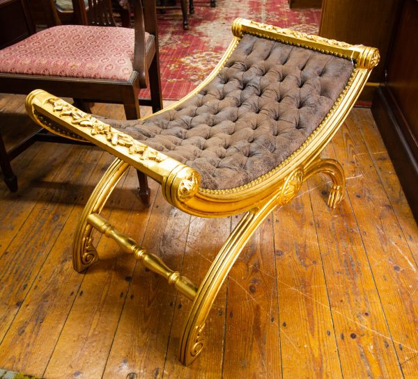 """Carved gilt frame, button top window seat with x-frame base. Measures 32""""L x 20""""D x 22""""H"""