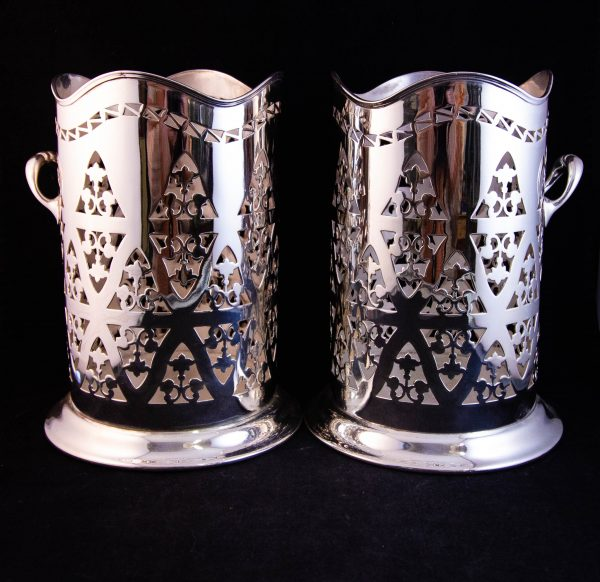 "Pair of silver plated pierced bottle coasters. Measures 6""W x 8""H"