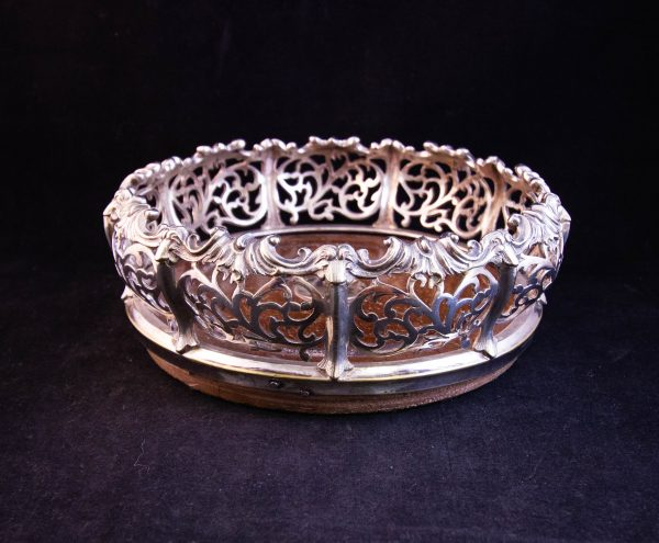 "Ornate silver plated bottle coaster with mahogany base. Measures 7.5""W x 3""H"