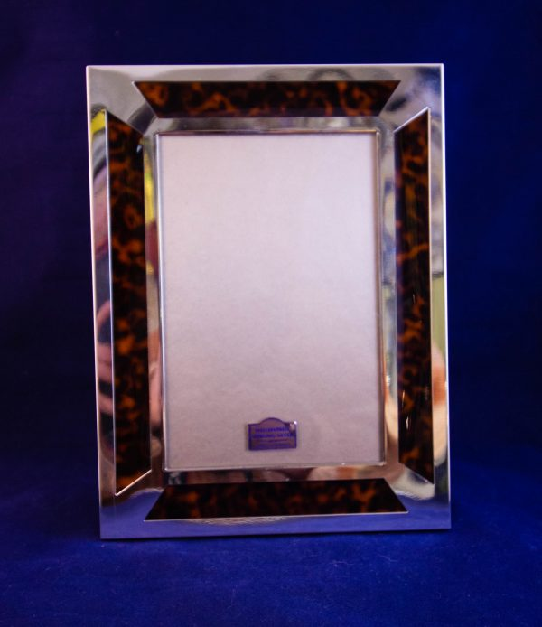 "Silver and faux tortoiseshell photo frame. Photo size measures 4""W x 6""H, total size measures 6.25""W x 8.25""H"