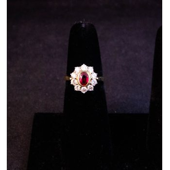 18k yellow gold ruby ring surrounded by 10 diamonds. Total diamond .65ct, total ruby .45. Size L. Price includes nationwide delivery.