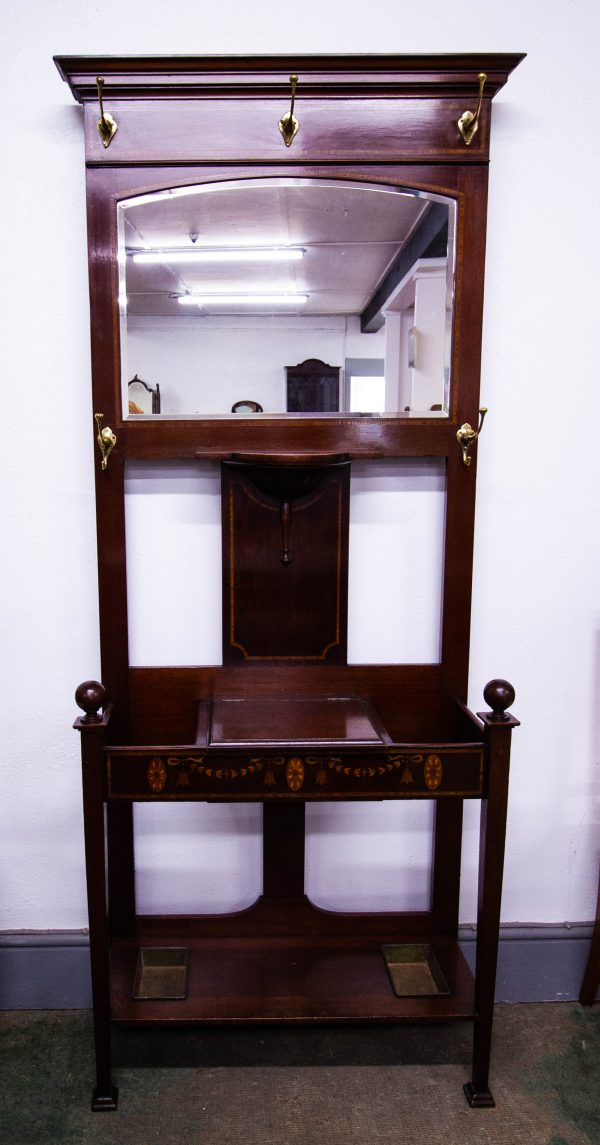 Inlaid mahogany hallstand with brass hooks, lift top and stick stand. Measures 87L x 33D x 193H cm. Price includes nationwide delivery.