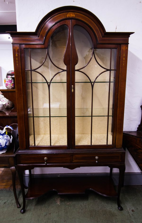 Shaped top inlaid mahogany display cabinet with two drawers. There is a small crack in the glass of the right hand door. Measures 106L x 40.5D x 194H in cm. Prices include nationwide delivery