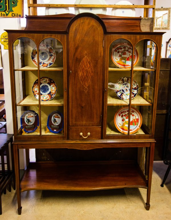 Inlaid mahogany display cabinet with shelf bottom. Also features an unusual blind door centre and drawer. Measures 122W x 38D x 183H in cm. Price includes nationwide delivery