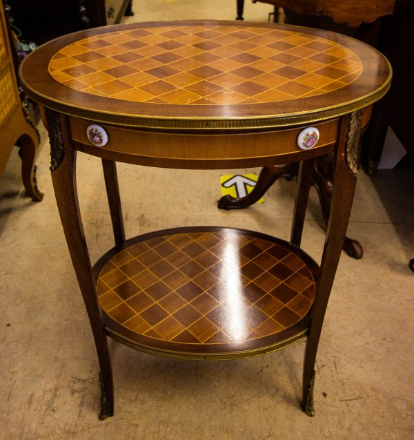 Inlaid oval two tier table, brass bound with porcelain button details. Measures 55W x 42.5D x 67H in cm. Price includes nationwide delivery